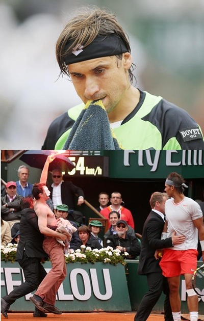 David Ferrer (above) Rafael Nadal of Spain looks on as security guards restrain a protester after he lit a flare and ran on   court
