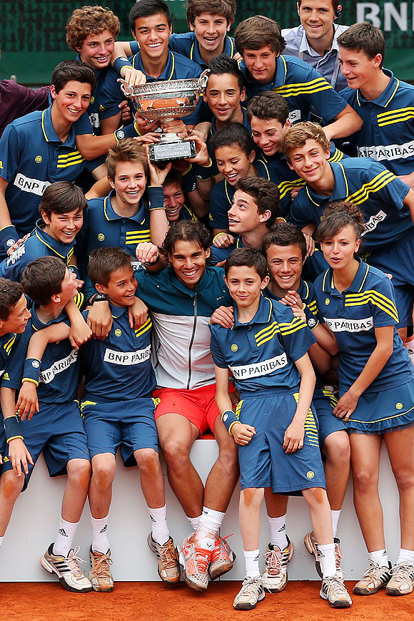 Rafael Nadal of Spain poses with the ballboys, ballgirls as he celebrates his French Open victory on Sunday