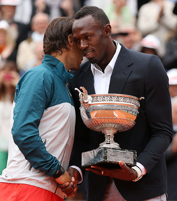 Rafael Nadal of Spain is presented with the Coupe des Mousquetaires trophy by Usian Bolt after the men's singles final against David Ferrer on Sunday
