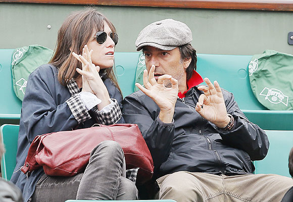 French actress and singer Charlotte Gainsbourg (lrft) and her husband French actor and director Yvan Attal watch the men's singles final on Sunday