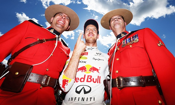 Sebastian Vettel celebrates with two Canadian Mounties