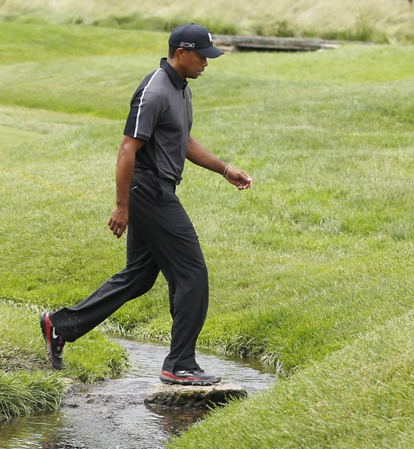 Tiger Woods of the US crosses a creek