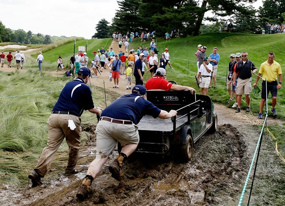 Staff help push a golf cart through the mud during the US Open at Merion Golf Club