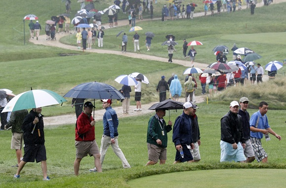 Spectators walk in the rain during the US Open golf championship at the Merion Golf Club in Ardmore