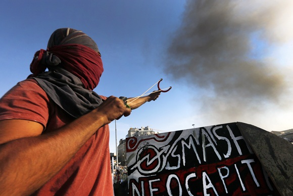 A protester uses a sling shot against police during clashes between police and anti-government protesters in Istanbul