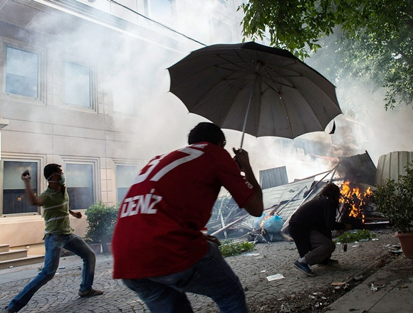 A protester throws an object from behind a burning barricade during a demonstration near Taksim Square