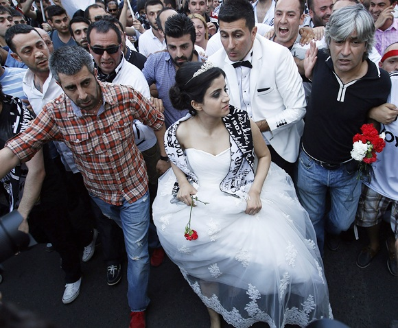 A newlywed couple joins protesters as they march towards Taksim Square in Istanbul