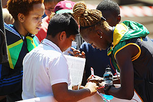 Dominique Blake of Jamaica signs autographs during a training session