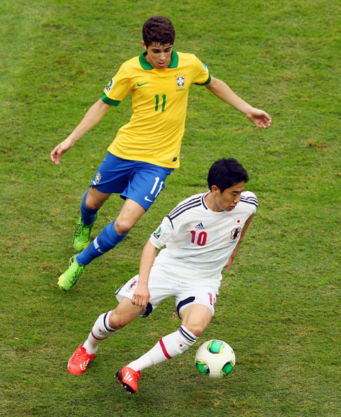 Japan's Shinji Kagawa gets the ball past Oscar of Brazil