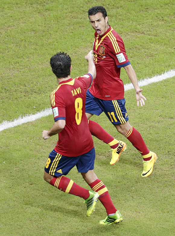 Spain's Pedro (right) celebrates teammate Xavi after scoring against Uruguay during their