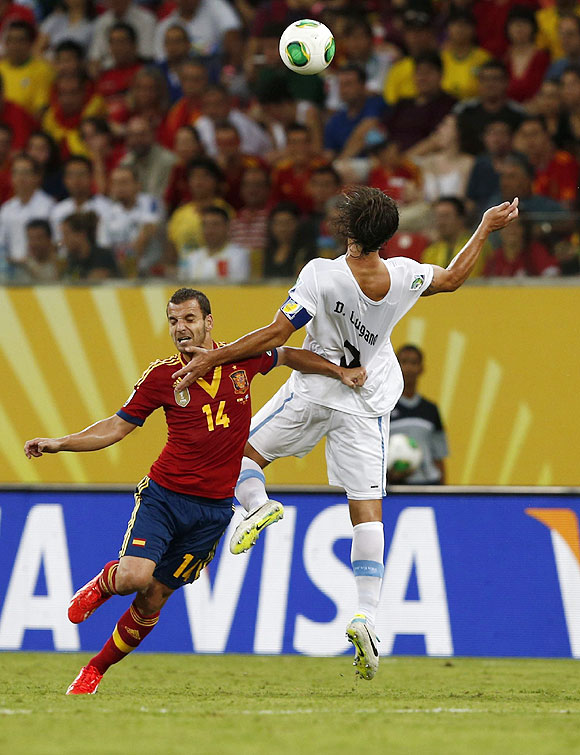 Spain's Roberto Soldado (left) and Uruguay's Diego Lugano fight for possession during their Confederations Cup Group B match at the Arena Pernambuco in Recife, Brazil on Sunday