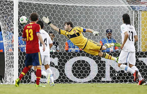 Spain's goalkeeper Iker Casillas (centre) dives full stretch but fails to make a save off a free kick goal by Uruguay's Luis Suarez during their Confederations Cup Group B match at the Arena Pernambuco in Recife, Brazil on Sunday