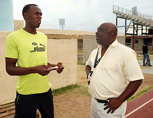 Coach Glenn Mills talks to Usain Bolt
