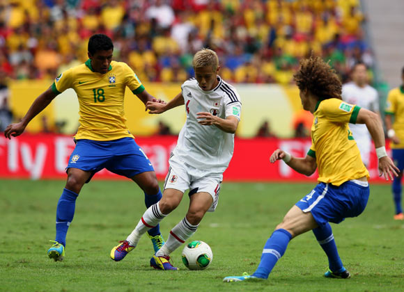 Japan's Keisuke Honda tries to get the ball past Paulinho and David Luiz of Brazil