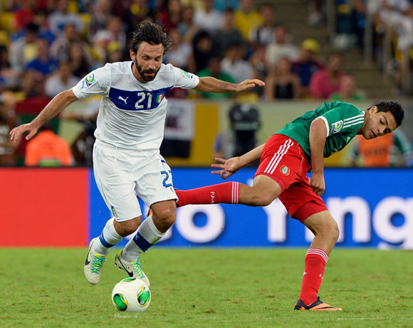 Andrea Pirlo dribbles the ball past Raul Jimenez of Mexico