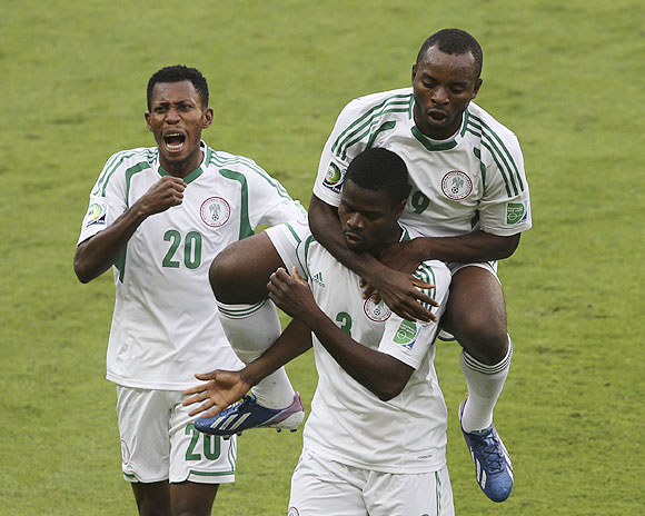Nigeria's Sunday Mba (top) celebrates with teammate Uwa Echiejile, who scored the team's first goal, against Tahiti during their Confederations Cup match at the Estadio Mineirao in Belo Horizonte on Monday