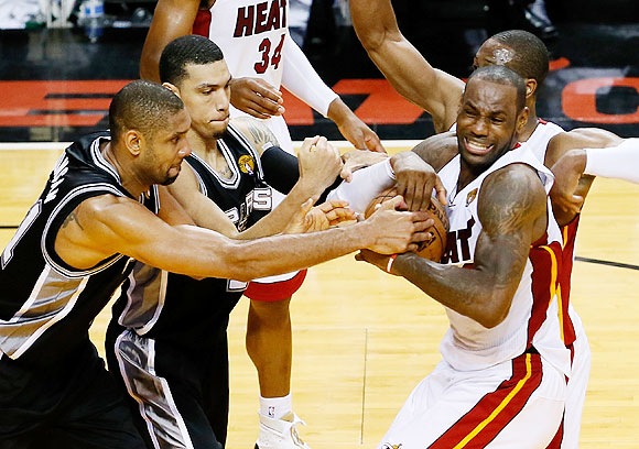 Tim Duncan and Danny Green of the San Antonio Spurs battle for the ball with LeBron James and Dwyane Wade of the Miami Heat in overtime during Game Six of the 2013 NBA Finals at AmericanAirlines Arena in Miami, Florida on Tuesday