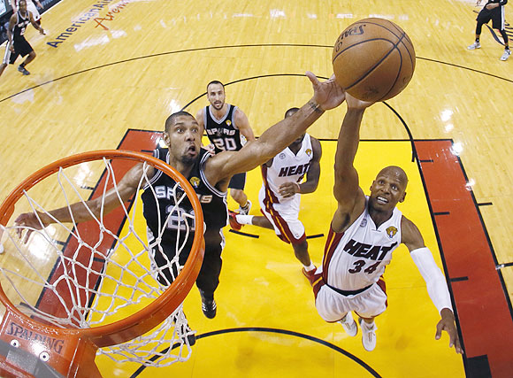 San Antonio Spurs power forward Tim Duncan (21) and Miami Heat shooting guard Ray Allen (34) reach for a rebound