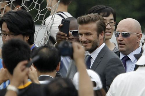 David Beckham arrives at Tongji University, in Shanghai, surrounded by his fans