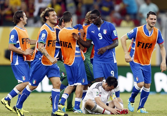 Italy's Mario Balotelli (9) celebrates with teammates as Japan's Shinji Okazaki reacts