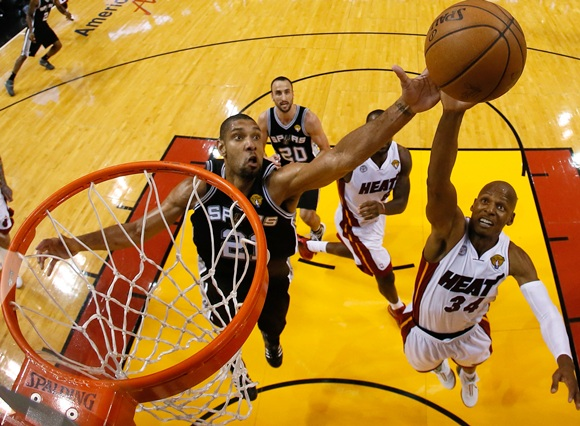 Tim Duncan (21) of the San Antonio Spurs and Ray Allen (34) of the Miami Heat go after a rebound