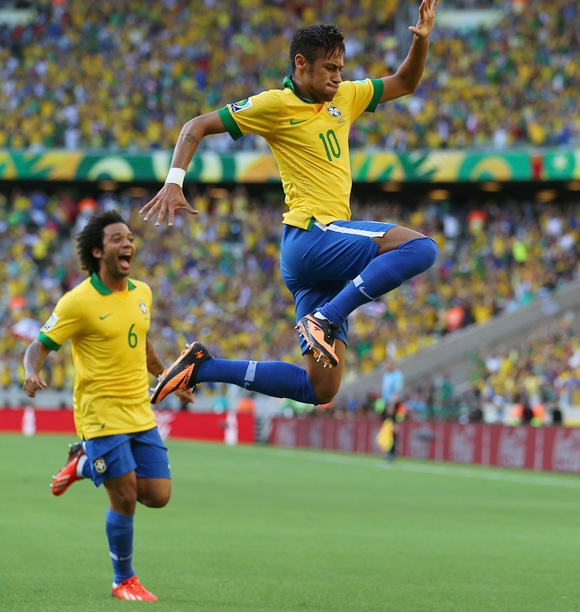 Neymar of Brazil celebrates scoring the opening goal with teammate Marcelo