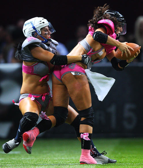 Ashley Salerno of the Western Conference QLD Reds loses her top as she is tackled by Theresa Petruziello of the Eastern Conference NSW Blues
