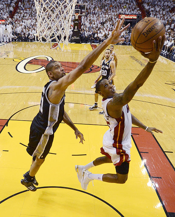 Miami Heat point guard Mario Chalmers (15) scores on a play past San Antonio Spurs power forward Tim Duncan (21) during Game 7 of their NBA Finals on Thursday
