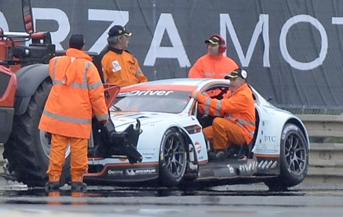 Security members work near the car of Denmark's Allan Simonsen during the Le Mans 24-hour sportscar race in Le Mans