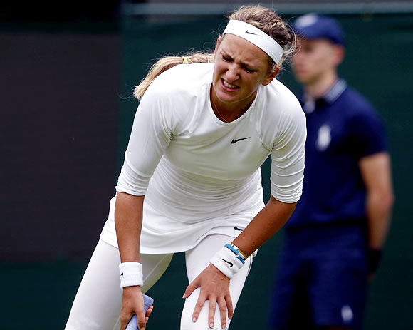 Victoria Azarenka holds her leg after injuring herself