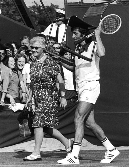 Ilie Nastase assists an elderly lady with her seat before a match, on July 2, 1975.