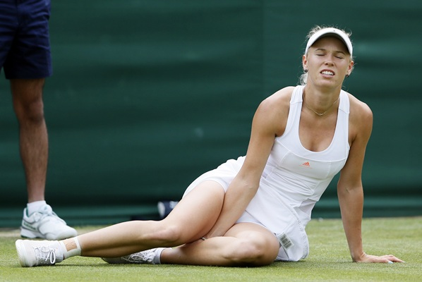 Caroline Wozniacki of Denmark holds her ankle after falling in her women's singles tennis match against Petra Cetkovska