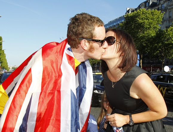 Bradley Wiggins of Britain wearing a British national flag kisses his wife