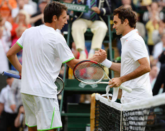 Sergiy Stakhovsky of Ukraine shakes hands at the net with Roger Federer of Switzerland after their match