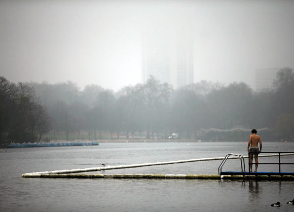 A man prepares for a foggy morning swim in the Serpentine Lake in Hyde Park, in London.