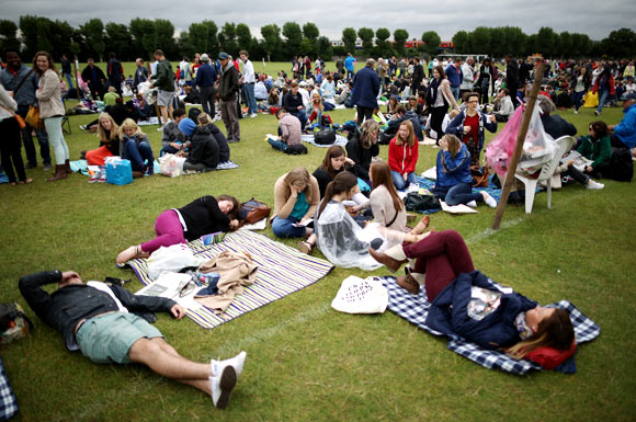 Non-ticket holders wait in line in a field outside Wimbledon