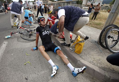 Team Sky rider Geraint Thomas of Britain sits on thy street after he fell at 5 kilometers from the finish of the 213 km first stage of the centenary Tour de France cycling race from Porto-Vecchio to Bastia