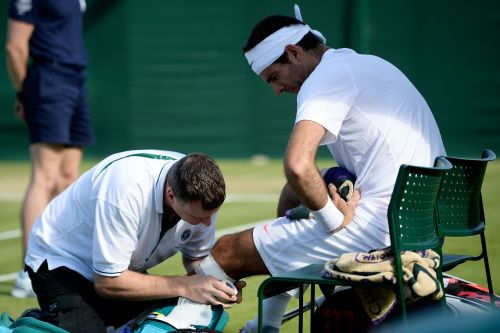 Juan Martin Del Potro of Argentina receives assistance during a break in the Gentlemen's Singles third round match against Grega Zemlja of Slovenia on day six of the Wimbledon Lawn Tennis Championships