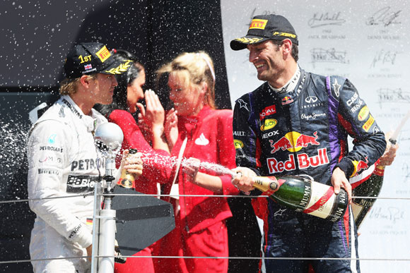 Race winner Nico Rosberg (L) of Germany and Mercedes GP celebrates on the podium with second placed Mark Webber at Silverstone Circuit