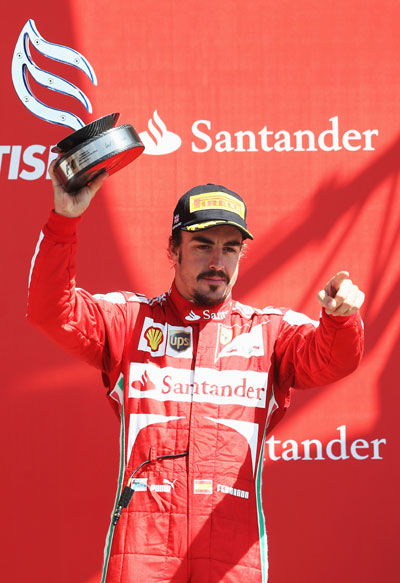 Fernando Alonso of Spain and Ferrari celebrates on the podium after finishing third