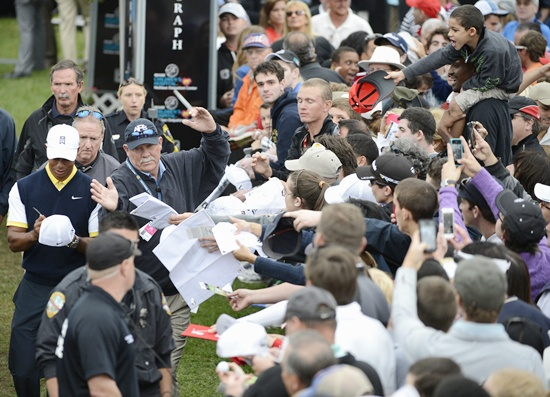Tiger Woods of the US (left) signs autographs for the fans
