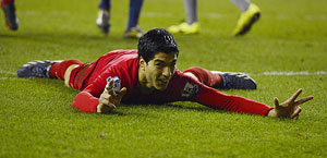 Luis Suarez celebrates after scoring a hat-trick against Wigan on Saturday