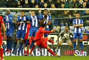 Liverpool's Luis Suarez scores the third goal from a free kick during their match against Wigan Athletic on Saturday