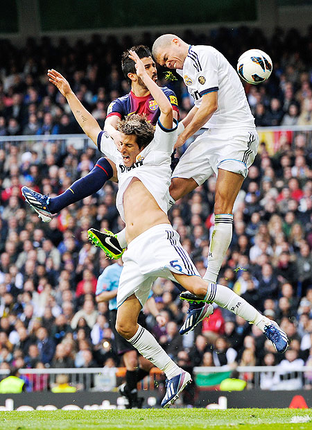 Barcelona's David Villa (centre) is involved in an aerial duel with Real Madrid's Fabio Coentrao and Pepe (right) during their 'Clasico' match on Saturday