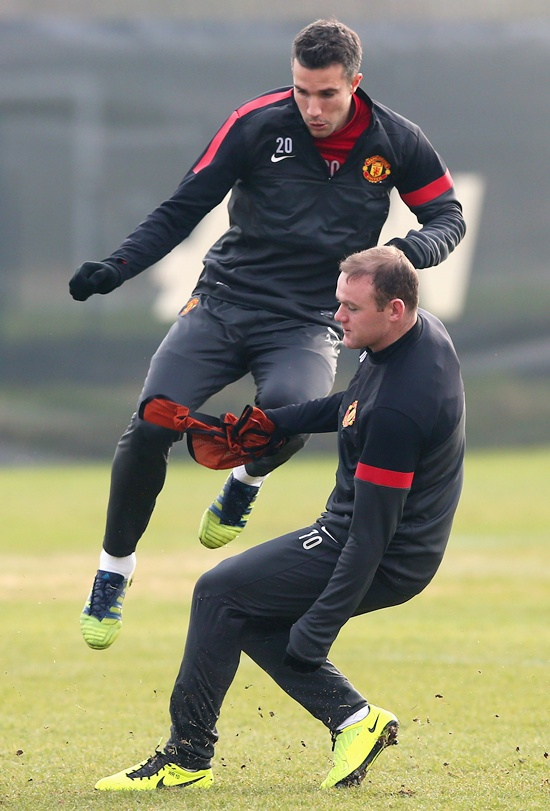 Wayne Rooney of Manchester United tackles Robin Van Persie