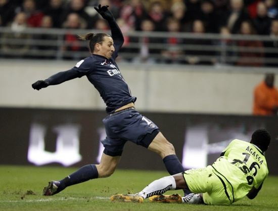 Kossi Agassa (right) of Stade Reims fights for the ball with Zlatan Ibrahimovic of Paris St Germain