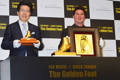 President and representative director of Ginza Tanaka Kikinzoku Jewelry KK, Masakazu Tanaka and Rodrigo Messi (R) pose with golden statue of the left foot of Lionel Messi
