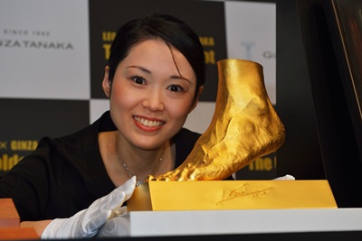 A woman poses with the golden statue of the left foot of Lionel Messi