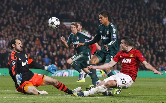 Manchester United's Robin van Persie (right) tries a shot against Real Madrid's goalkeeper Diego Lopez (left)
