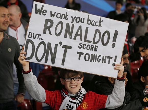 A Manchester United fan holds up a banner